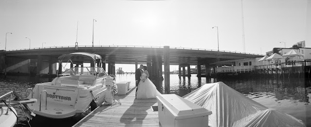 Jin and Christopher kiss outside on the dock with boats at their Bridgeview Yacht Club Wedding