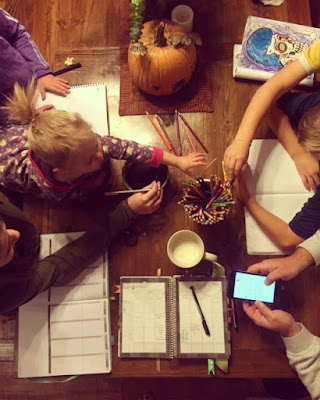 cute family gathered around the table planning out their week Mormon Mom Planner