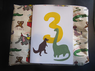 parcel with animal wrapping paper and card with yellow '3' and two dinosaurs
