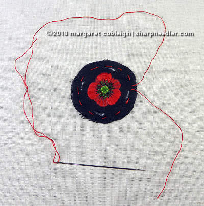 Cut out embroidered remembrance poppy with running string ready to be gathered and mounted in pin setting