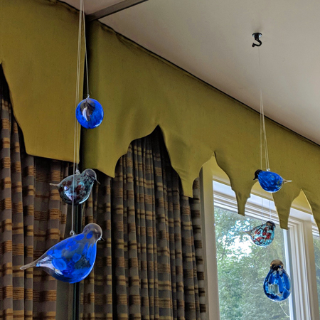 image of three glass birds hanging from a ceiling hook in our dining room, and reflected in a wall mirror
