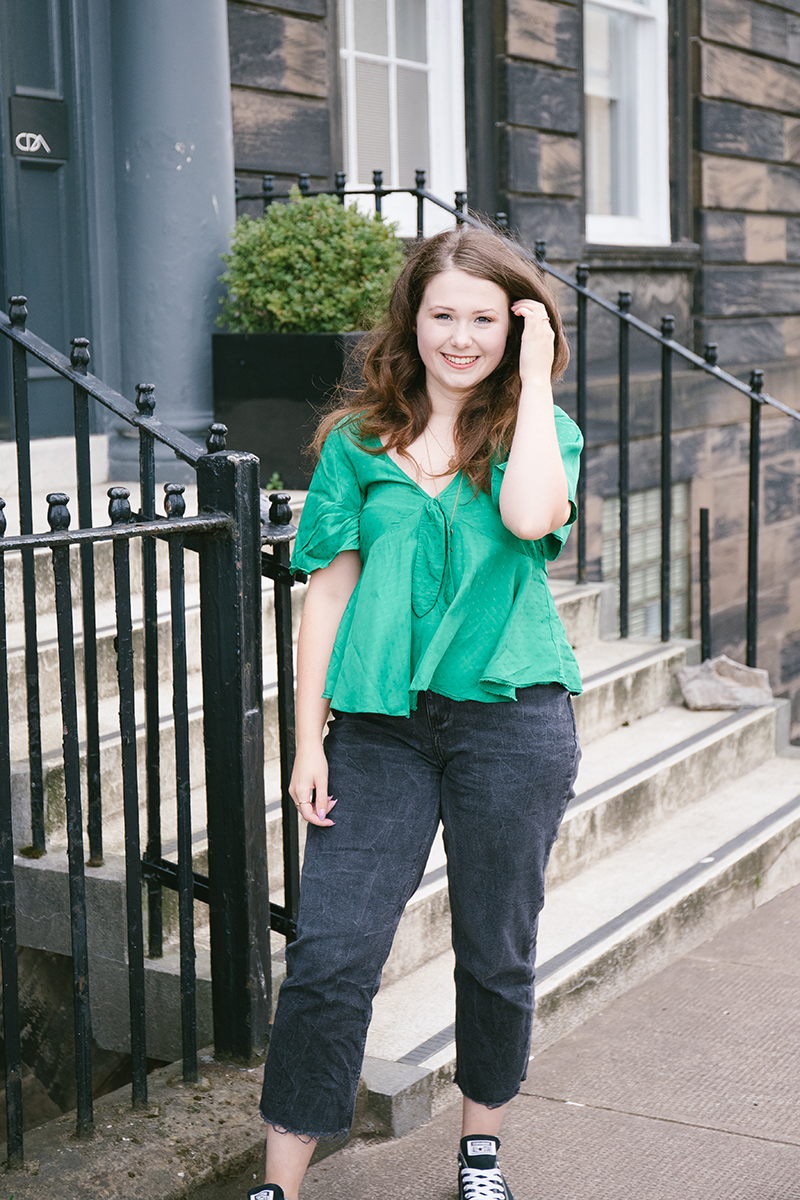 Young woman poses in street wearing green top and black jeans