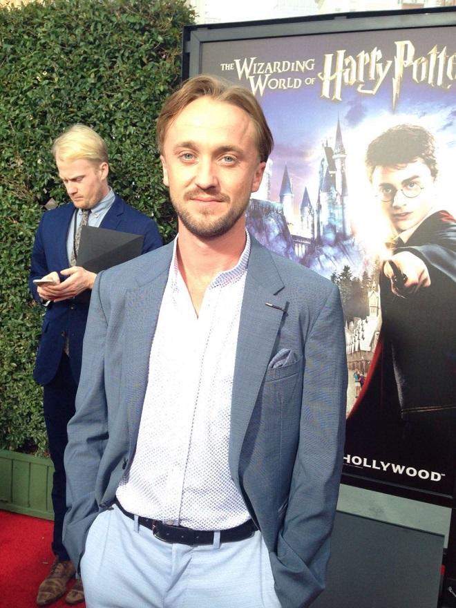 Tom Felton (Draco Malfoy) posando para foto no tapete vermelho de inauguração do parque.