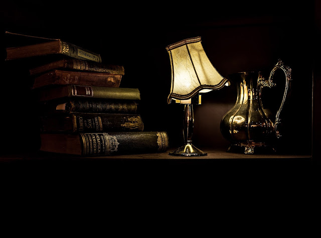 A wonky light next to some old books and jugs