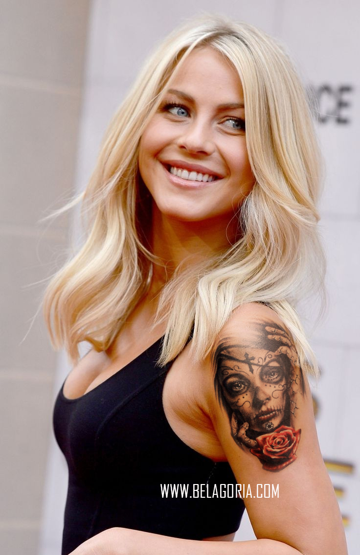 Mujer rubia, se gira para mirar sonriendo, lleva tatuaje de catrina en el brazo izquierdo