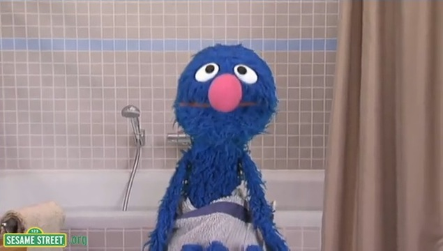 Grover wrapped in a towel standing in front of a bathtub
