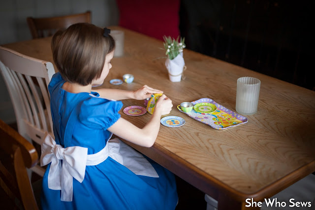 Girl in blue dress playing with her teaset