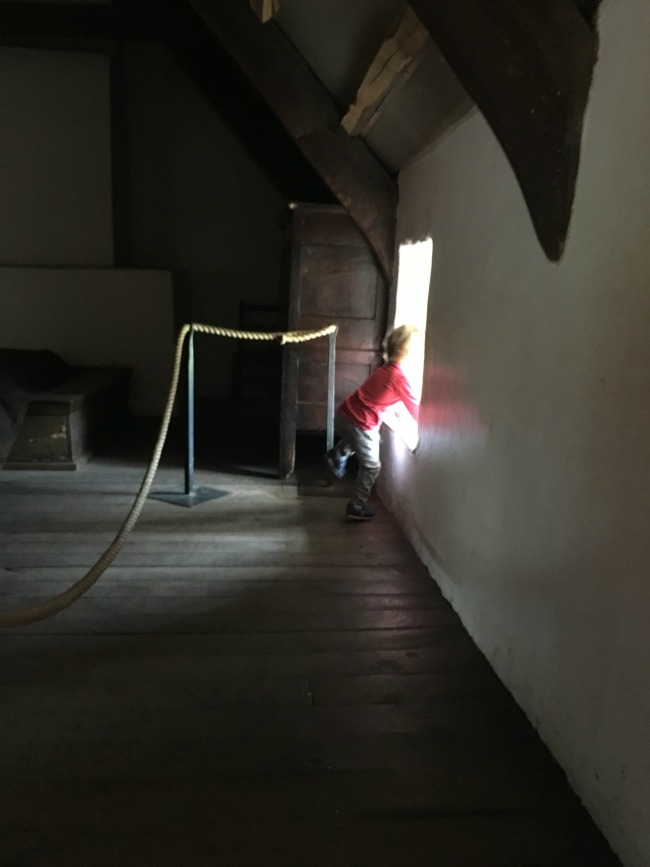 toddler-climbing-onto-window-sill-inside-cottage-at-St-Fagans