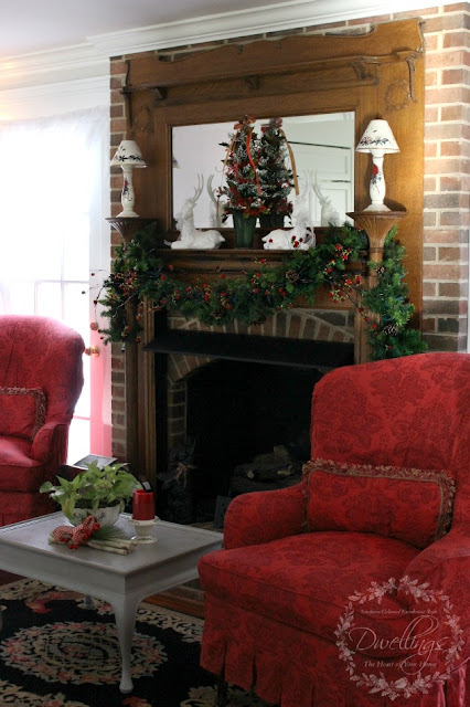 Farmhouse kitchen mantel with garland, Christmas tree and two white deer.