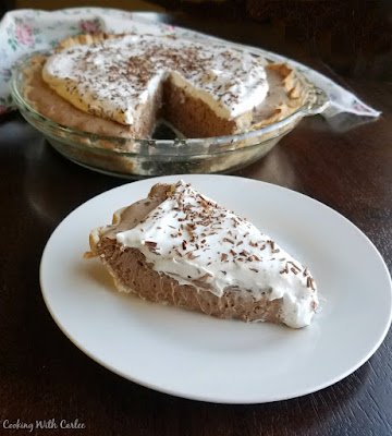 slice of french silk pie served on white plate with remaining pie in background