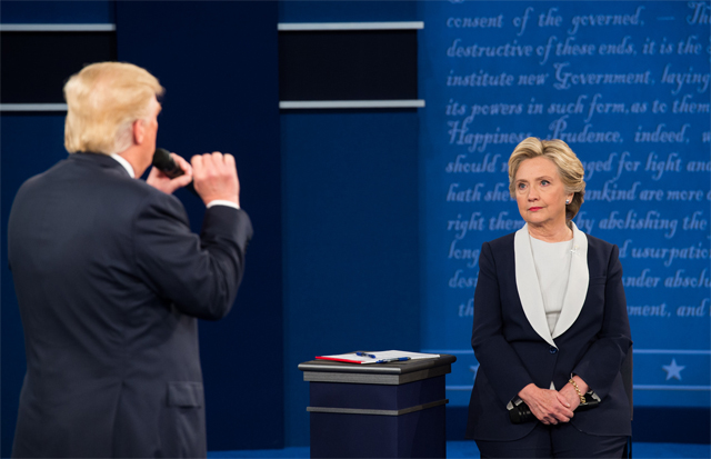 image of Hillary Clinton and Donald Trump from the second presidential debate; Trump is standing and speaking into a mic with his back to the camera; Clinton is sitting on a stool, looking at him with disgust