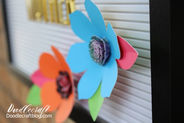 Brightly colored 3D flowers made with paper and placed on a DCWV letterboard