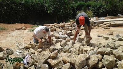 Bizzarri preparando as pedras moledo para iniciar o revestimento de pedra na parede da adega com pedra moledo.
