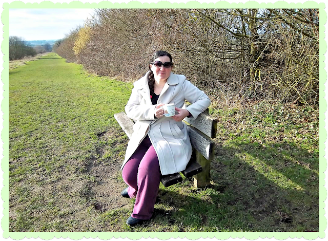 Female seated on bench in countryside with tea cup.