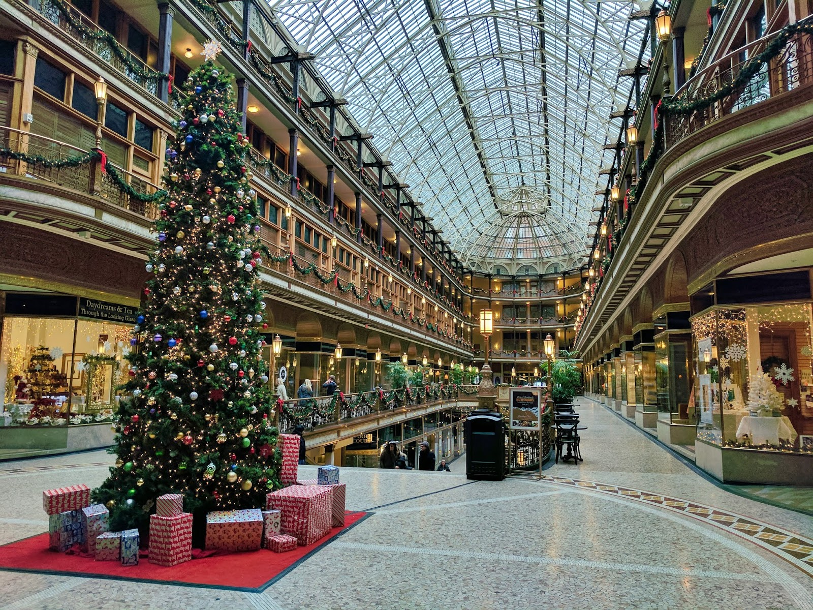 A photo of the inside of a shopping mall decorated for Christmas, on the top floor, taken from the right corner of a length of shops. A Christmas tree with presents around the bottom of it is on the left hand side, just in front of a long opening in the floor, where shoppers are coming up on an escalator.