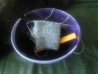 A textured mitten in progress on circular needles.  The yarn is fingering weight, and grey with specks of other colours. The yarn and mitten are in a purple ceramic yarn bowl, along with a small wooden ruler.