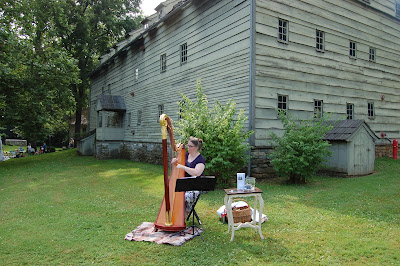 Woman playing a harp on the grounds of Ephrata Cloister with building in background