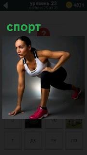 Молодая девушка в спортивной форме приготовилась к старту для забега на дистанцию