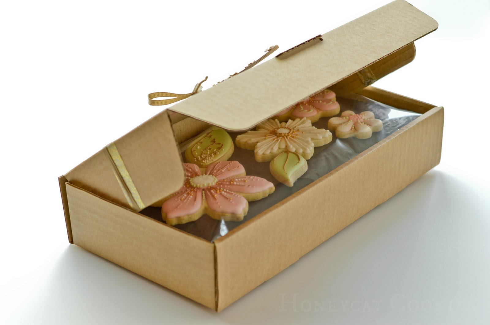 Partly open gift box showing sealed top layer of decorated cookies on cushion padding, by Honeycat Cookies.