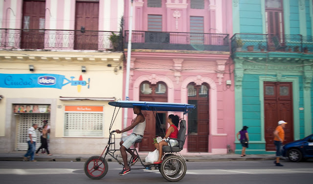 A bicitaxi carries passengers in Old Havana, Cuba