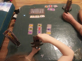 A game of Swordcrafters in progress, seen from above as two pairs of arms manipulate their swords. A third sword stands nearby on the table. Some tiles are still on the table waiting to be claimed, as the score tracker and three sword magic cards sit nearby.