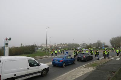 3 voitures approchent un rondpoint bloqué s par manifestants portant les gilets jaunes