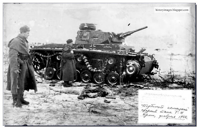 Russian soldiers examine wrecked German Panzer 3