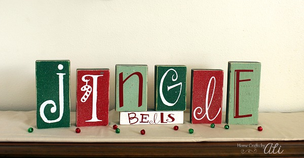 Do It Yourself Jingle Bells blocks painted and on holiday decor display.