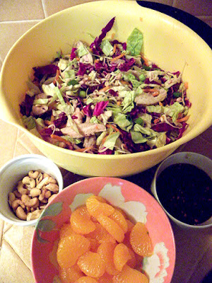 Large Bowl of Salad with Smaller bowls of Oranges, Cashews, and Dressing