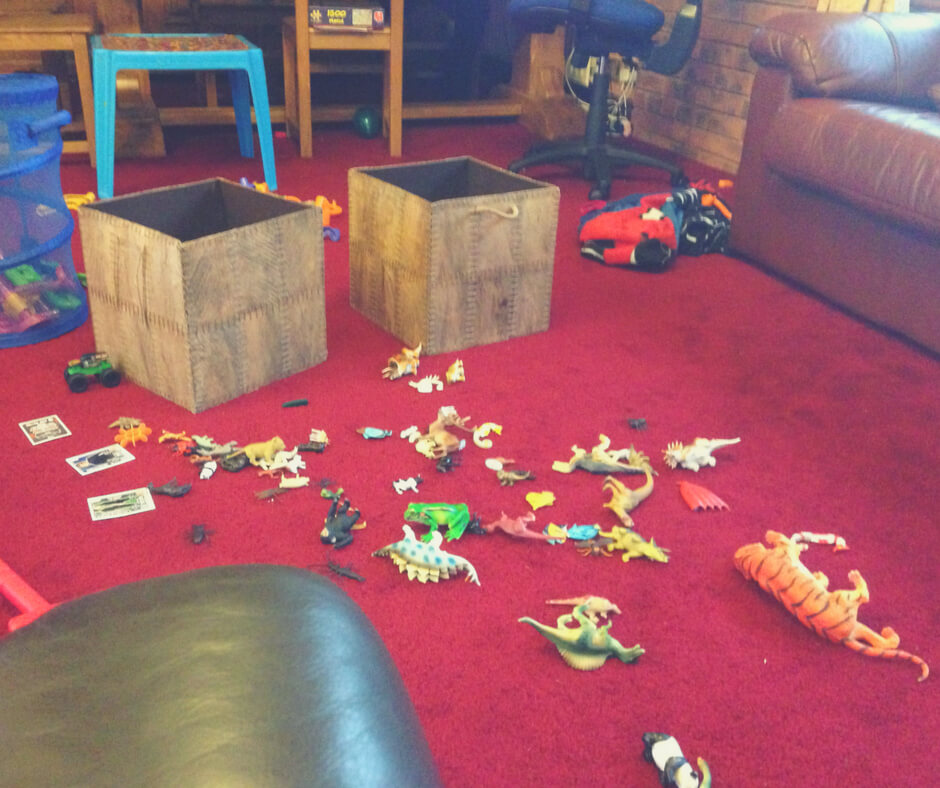 "Toy dinosaurs spread across a red carpet. Two brown boxes stand empty next to the pile of dinosaurs. Image for ""Why I give my children chores."""
