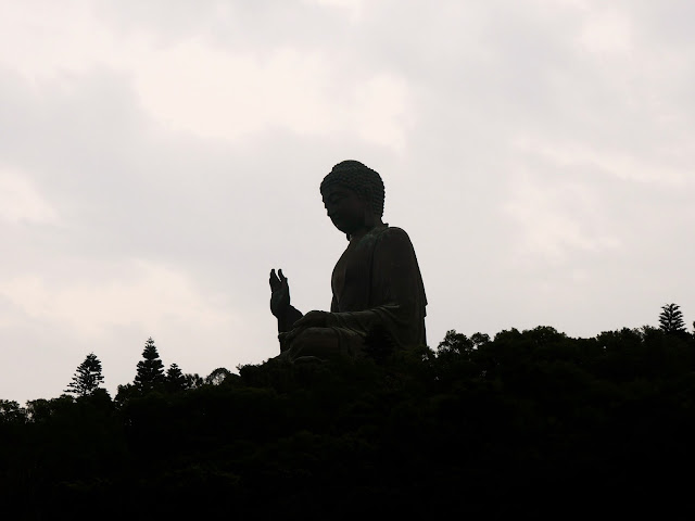Big Buddha / Tian Tan Buddha statue silhouette on the hill overlooking Ngong Ping, Lantau Island, Hong Kong