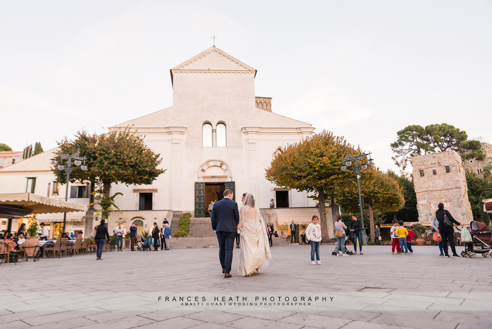 Bride and groom walking infront of Ravello church