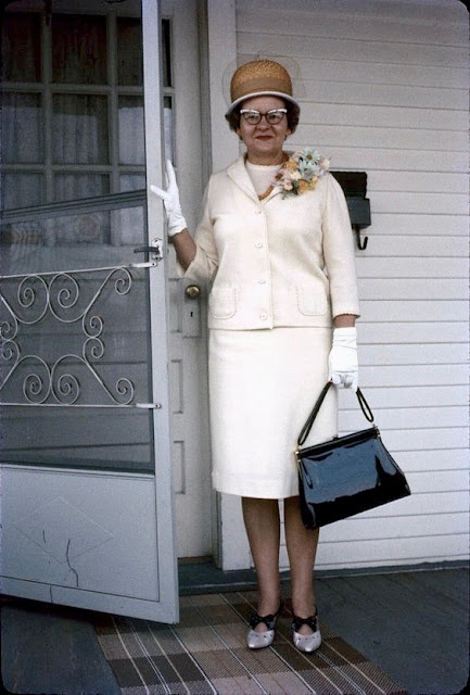 Snapshot of grandma in Sunday best standing on the front porch. 1950s cateye glasses and pillbox hat. Good Heavens and Other stories of Matronly Women. marchmatron.com