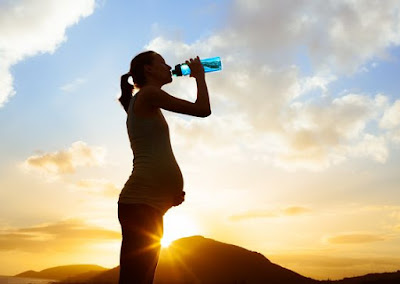 a pregnant is drinking water at sunrise time