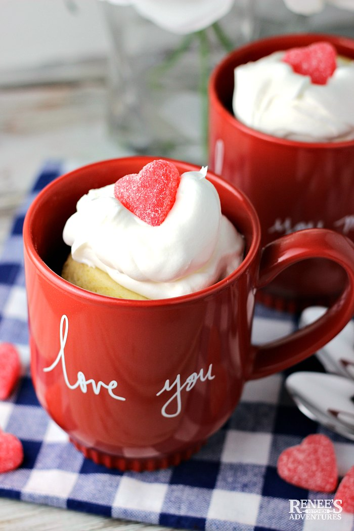 Two Vanilla Cake in a Mug on a blue and white checked cloth with whipped topping and gummy hearts