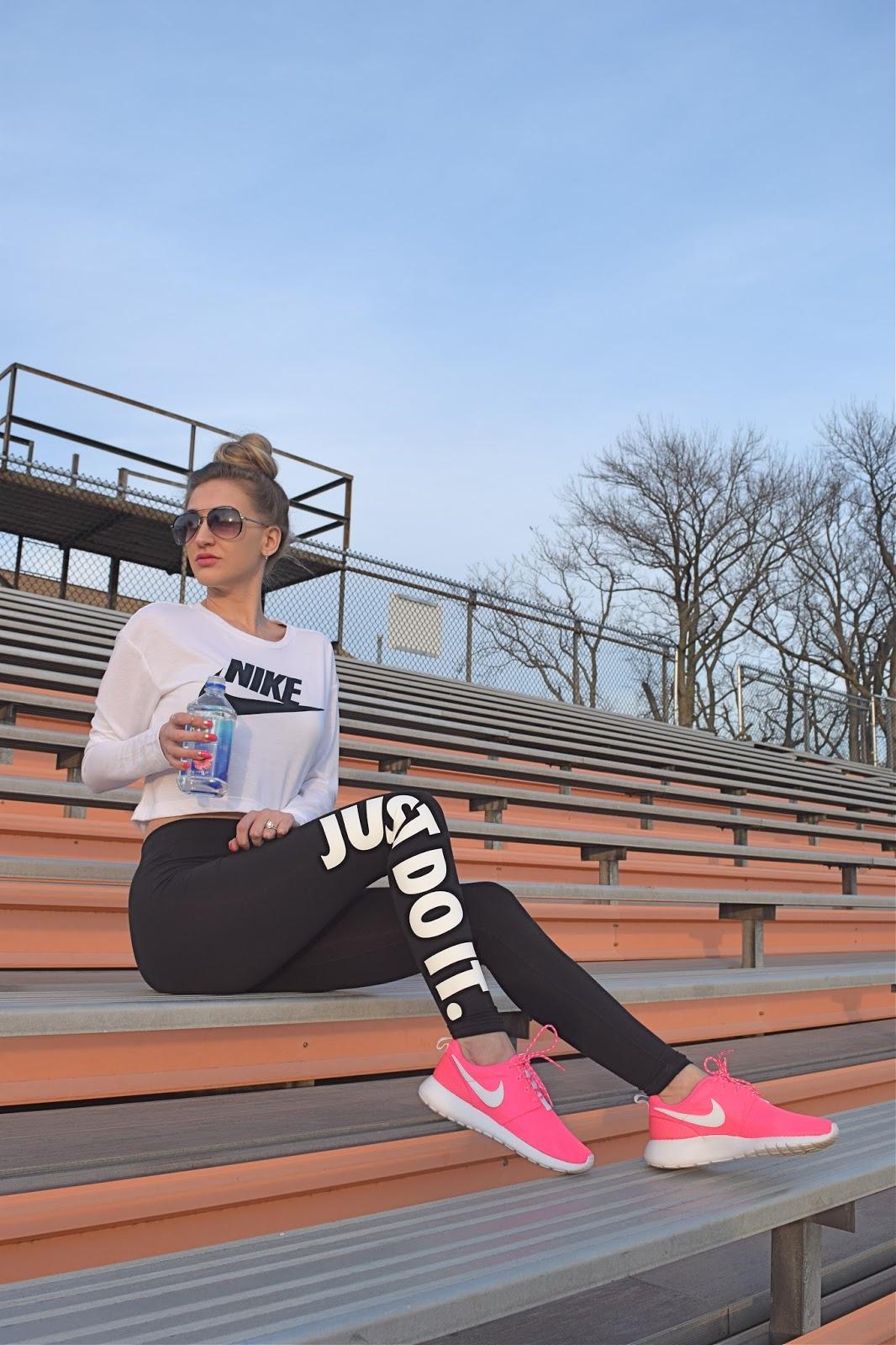 wearing Nike graphic crop top, Nike just do it jersey leggings, Pink Nike Roshe one sneakers, cute workout look, pink workout sneakers, nike workout blogger look