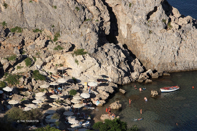 Tiny beach with sun umbrellas, a few people and a boat in the blue water, next to rocky cliffs..