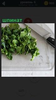 На разделочной доске лежит шпинат и рядом положен нож для приготовления