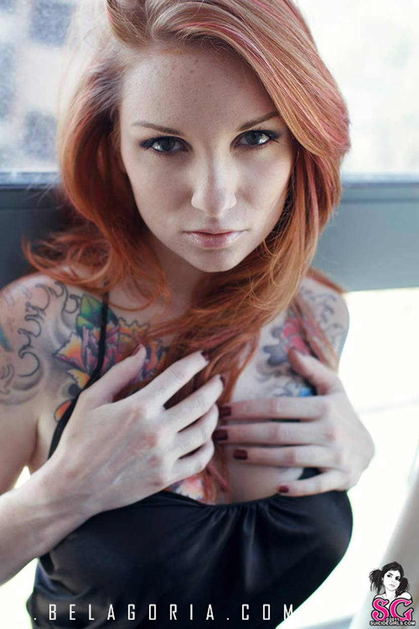 Foto de una mujer pelirroja con tatuajes de claveles