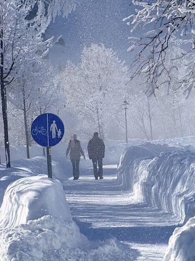 Foto de personas caminando bajo la nieve