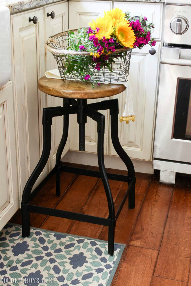 Flowers in wire basket on stool in farmhouse style kitchen