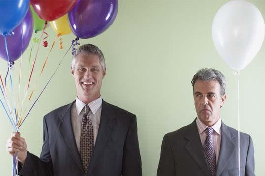 Hombre envidiando a otro porque tiene mas globos