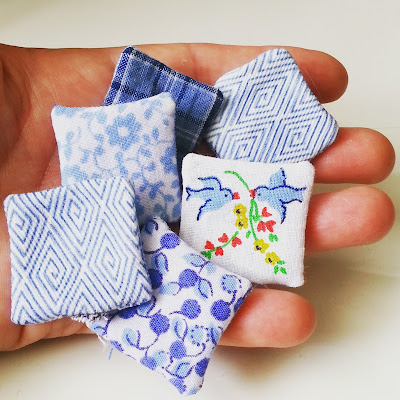 Six unstuffed  dolls' house miniature cushions, in shades of blue and white, on an outstretched hand.