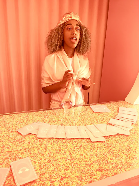 Fortune teller with cards in front of her standing at a countertop full of sprinkles