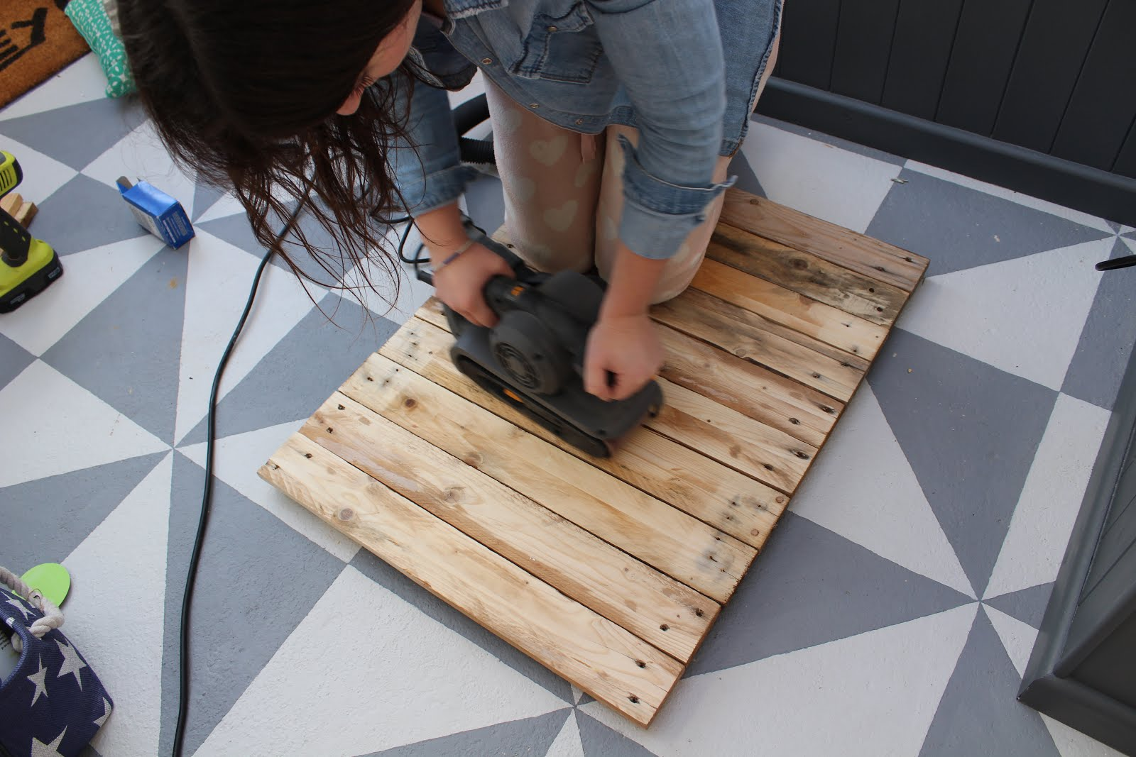 using a belt sander to sand pallet wood