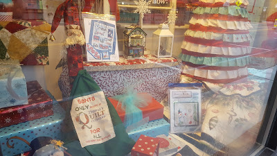 one of the storefront windows at Emma's Quilt Cupboard and Sewing Center