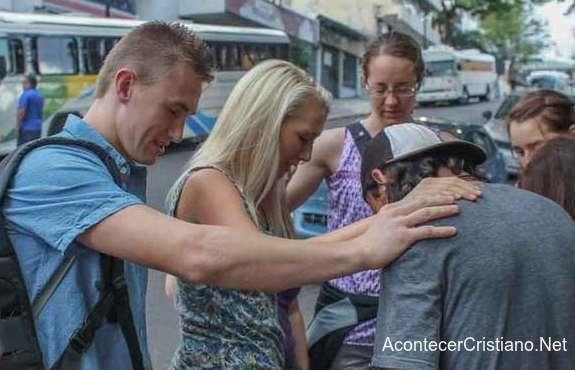 Jóvenes orando por personas en la calle