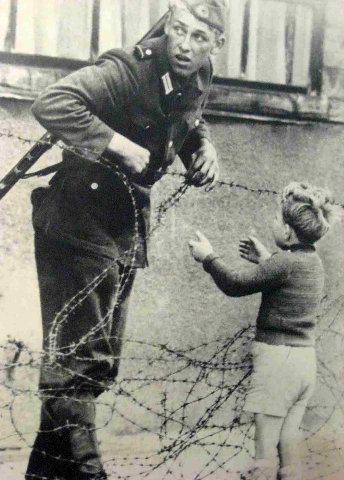 East German soldier helps a little boy sneak across the Berlin Wall, August 13, 1961.