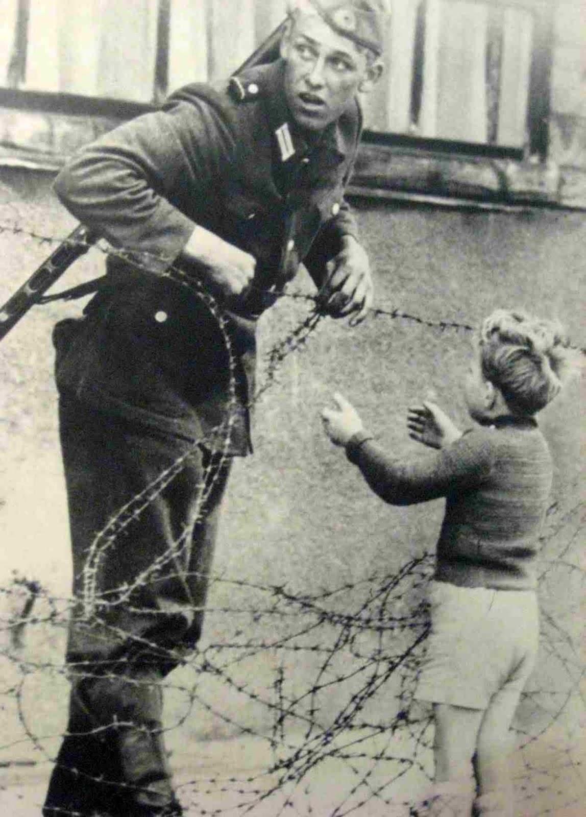 East German soldier helps a little boy sneak across the ...