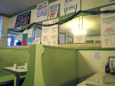 Interior shot of Bonnie's Cafe with light green painted booths and mirrored walls, lots of signs hanging